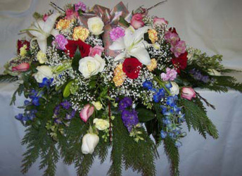 Rainbow of Colors Casket Spray from Clark Flower and Gift Shop in Clark, SD